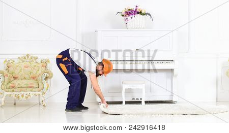 Relocating concept. Loader wrappes carpet into roll. Man with beard, worker in overalls and helmet rolling carpet, white background. Courier delivers furniture in case of move out, relocation. poster