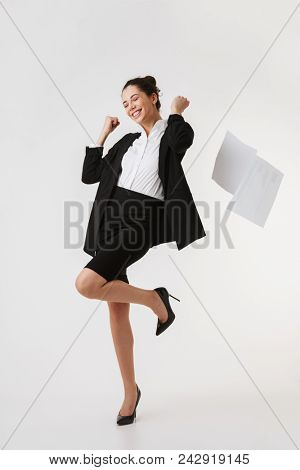 Full length portrait of an excited young businesswoman celebrating success isolated over white background