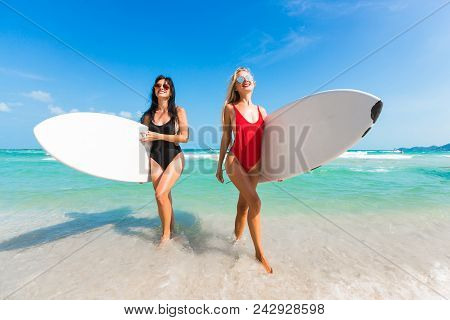 Two Beautiful Amazing Tanned Girls Surf, Blonde And Brunette, Run Out Of The Sea With Surfs Under Th