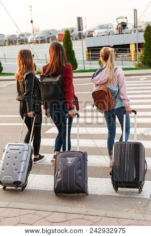 Portrait of three caucasian women from back traveling abroad together carrying luggage to airport. Air travel or holiday concept