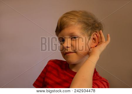 The Boy Listens Very Attentively. He Listens Very Attentively. He Pushes His Ear And Listens. His Fa