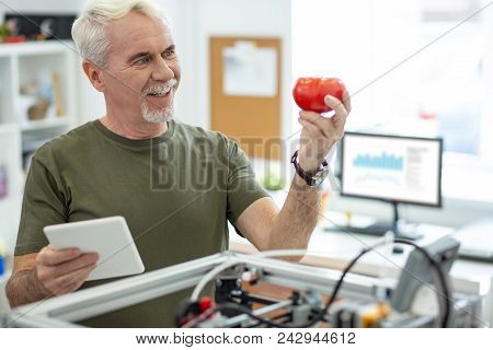 Great Results. Upbeat Senior Engineer Holding A Colorful Tomato Model And Smiling Widely While Looki