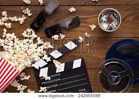 Cinema Background, Top View. Clapperboard, Popcorn, Soda And 3d Glasses On Wooden Table. Movie Goers