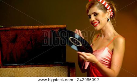 Retro woman with music vinyl record. Pin-up retro female style. Pin-up portrait of girl style wearing red dress. Retro style is one of the most popular styles.