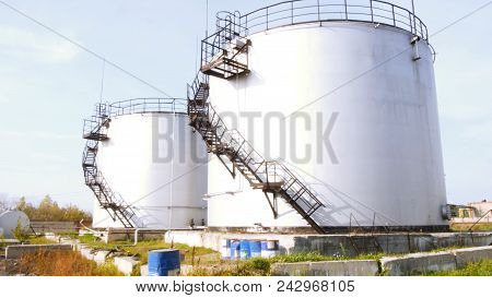 Large White Industrial Tanks For Petrol And Oil. Stock. Fuel Tanks At The Tank Farm. Big Industrial