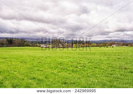A Small Village In Scottish Highlands At A Distance Under Cloudy Sky