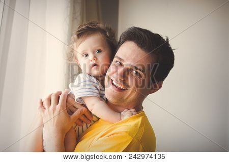 Young Brunet Father In Yellow Shirt Playing With A Little Baby At Home.