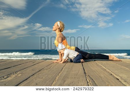 Baby Boy Playing With Mother On The Beach, Summer Day. Supermom With Toddler Son Learning Yoga On Wo