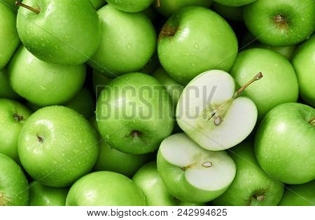 Bright Fresh Green Apples In Droplets Of Water, In The Middle Of A Cut Apple, Food Background Green