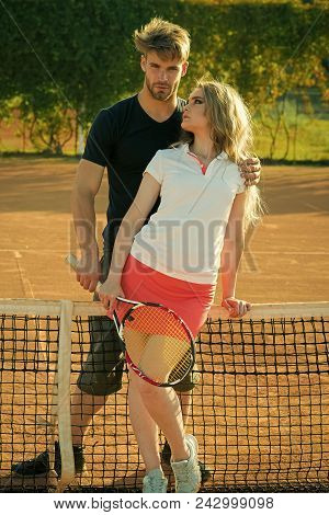 Couple In Love. Couple In Love Stand At Tennis Net On Clay Court. Woman And Man Athletes Hold Tennis