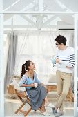 Young Vietnamese couple joking and drinking coffee poster
