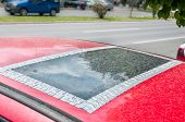 Damaged glass roof window or sunroof on the red car glued with duct tape to prevent water to come in the interior of the vehicle poster