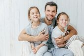 Father and kids. Paternity concept. Handsome unshaven affectionate dad embraces his two pretty dauhters, going to have walk together, have good relationship, pose at camera with positive smiles poster