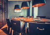 Stylish inside decor of the mod restaurant. The contemporary interior the wooden round table, comfortable chairs and the modern lamps. Exquisite combination the royal blue and orange shades. poster