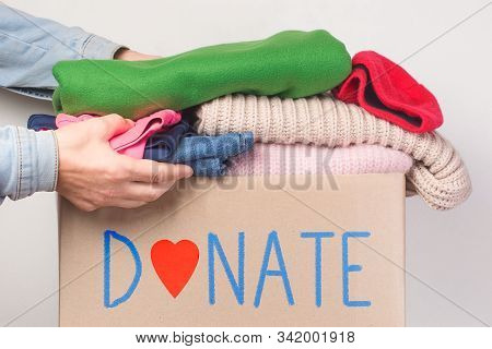 Donation Concept. Donation Box With Donation Clothes On A  Charity. Helping Poor And Needy People.