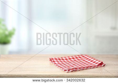 Red Checkered Folded Picnic Cloth On Wooden Table Empty Space Background.towel Over The Plank Blurre