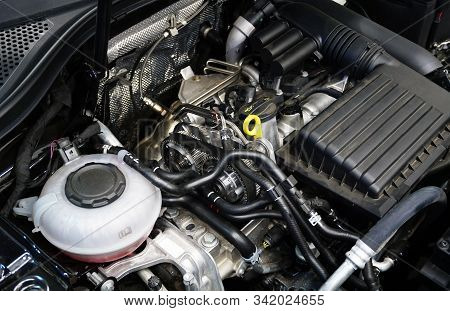 The Engine Compartment And Engine Of A Modern Car. In The Center Of The Frame Are Gears And Timing B