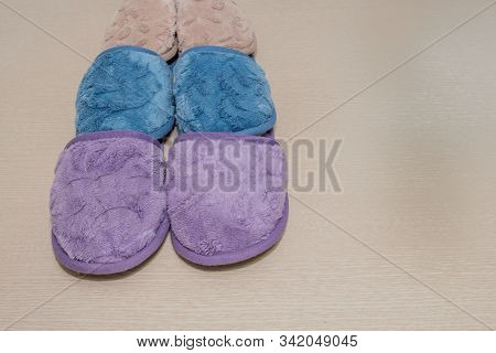 Closeup Of Pair Of Purple, Pair Of Dark Blue And Pair Of Brown Slippers Together On Light Wood Grain