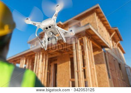 Pilot Flies Drone Quadcopter Inspecting Home Construction Site.