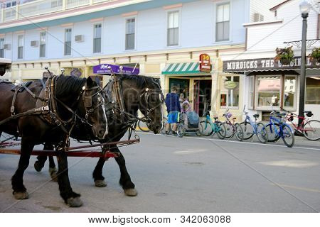 Mackinac Island, Michigan / United States - June 11, 2018: Draught Horses Pull Carriages Through Dow