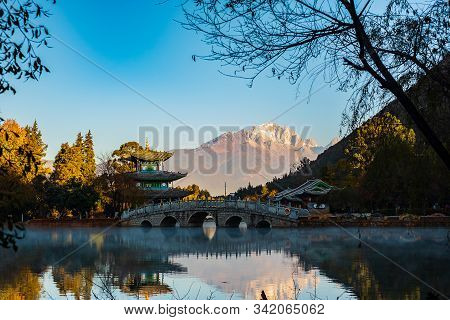 Black Dragon Pool With Jade Dragon Snow Mountain Background, Landmark And Popular Spot For Tourists