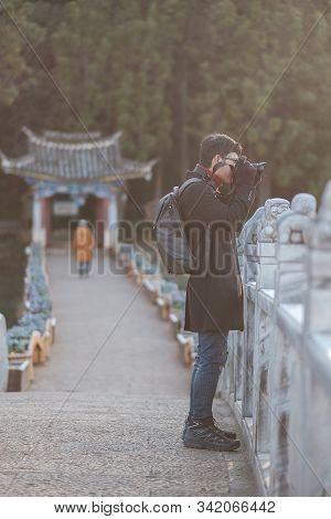Young Man Traveler Traveling At Black Dragon Pool With Jade Dragon Snow Mountain Background, Landmar