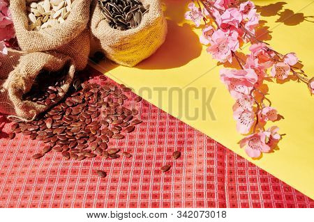 Table Served For Tet Celebration With Blooming Peach Branches And Sacks With Watermelon, Sunflower A