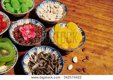 Sunflower, Watermelon And Pumpkin Seeds And Dried Fruits In Small Bowls On Wooden Table For Tet Cele