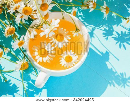 Herbal Tea With Fresh Chamomile Flowers. Cup Of Medicinal Chamomile Tea On A Bright Turquoise Backgr