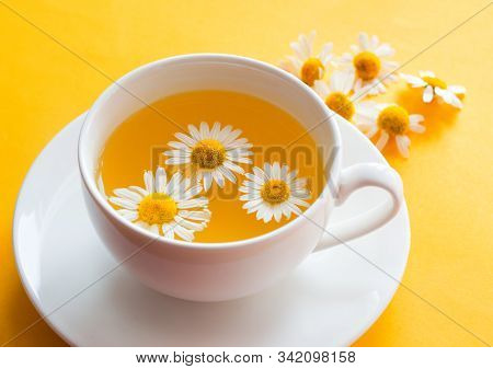 Herbal Tea With Fresh Chamomile Flowers In A Cup. Cup Of Medicinal Chamomile Tea On A Bright Yellow