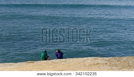 A Couple Of Beachgoers Sitting  At The Edge Of Sunset Cliffs Bluffs, San Diego