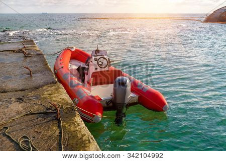 Red Rescue Inflatable Boat Moored To The Sea Pier, Closeup. Empty Marine Rescue Boat