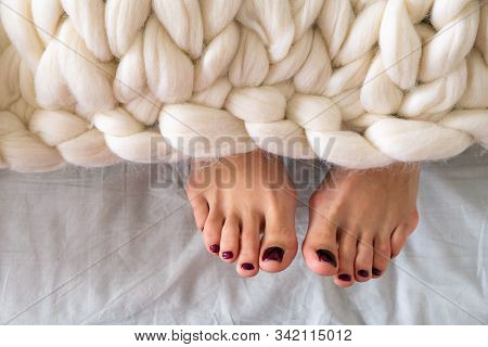 Legs Sticked Out From The Knitted White Merino Wool Plaid