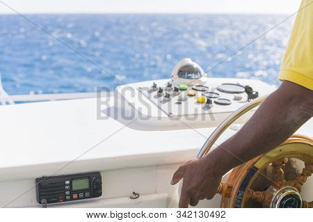 Hand Of Captain On Steering Wheel Of Motor Boat In The Blue Ocean During The Fishery Day. Boat Or Ya