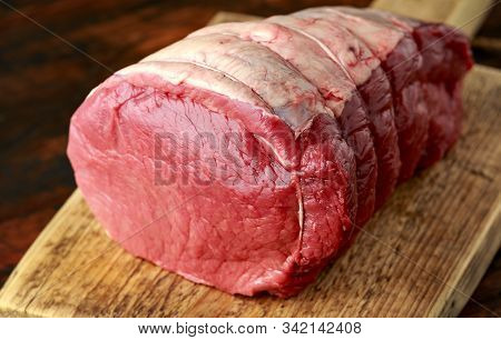 Butcher Slicing Fresh Raw Top Side Beef Meat On Rustic Wooden Chopping Board