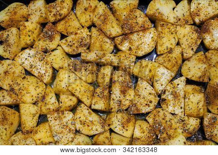 Texture Of Raw Potatoes Pieces Sprinkled With Seasonings Before Baking. Chopped Cubical Potato In Co