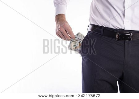 Businessman Pulls Out A Pack Of Dollars From His Trouser Pocket Closeup On A White Background With S