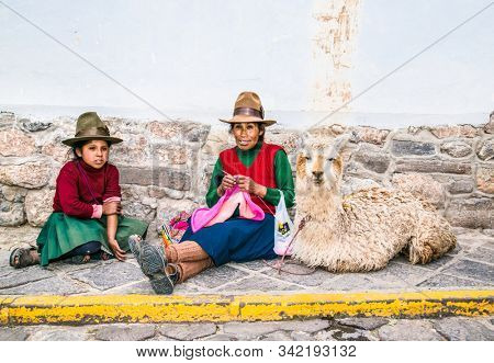 Cusco , Peru- Jan 9, 2019:  Old Quechua woman with lama and yong girl  knits at street of Cusco. Peru.