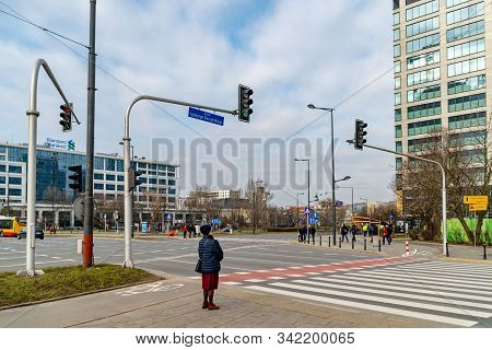 A Woman Stands In Front Of A Pedestrian Crossing In Anticipation Of The Green Light Of A Traffic Lig