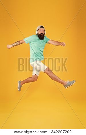 Energetic And Upbeat Music For Leisure. Energetic Hipster Jumping High On Yellow Background. Bearded