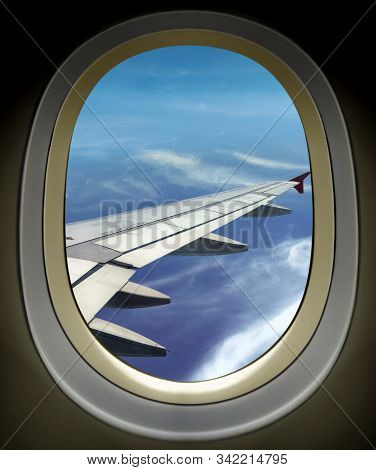 Airplane Window Wing View And Bright Cloudy Blue Sky