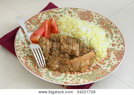 A plate of chicken and lentil curry, chicken dhansak, served with yellow and white rice and tomato