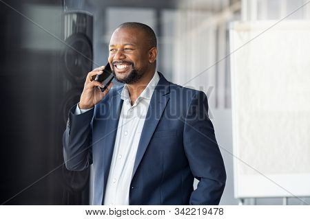 Successful black businessman in a happy conversation over cellphone. Mature african american business man in formal suit talking over phone in modern office. while looking through the window.