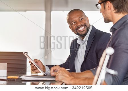 Business partners working on project together. Smiling african businessman working and discussing with employee in modern office over a report. Happy and successful leader with colleague in conference