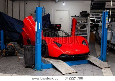 Novosibirsk, Russia - 08.01.2018: Red Sports Car Marussia B1 Raised On A Lift In A Car Repair Shop,