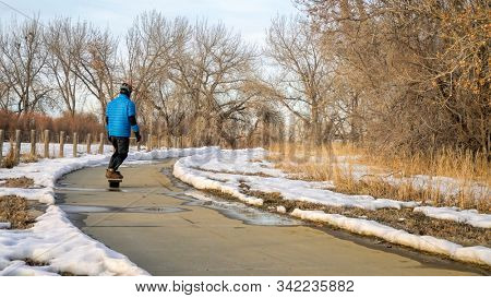 male rider is commuting on electric skateboard along bike trail in winter scenery in northern Colorado - Colorado Front Range Trail in Boyd Lake State Park