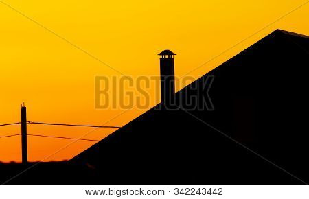Silhouette Of A Chimney On The Roof Of A House Against The Backdrop Of A Sunset.
