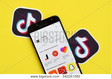 Tiktok Application In Playmarket On Samsung Smartphone Screen On Yellow Background. Tiktok Is A Popu