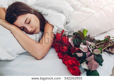Valentines Day. Woman Sleeping By Bouquet Of Red Roses In Bed At Home. Boyfriend Or Husband Gifted F