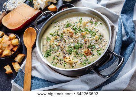Close-up Of Creamy Roasted Garlic Cauliflower Soup With Asiago Cheese In A Stockpot With Ingredients